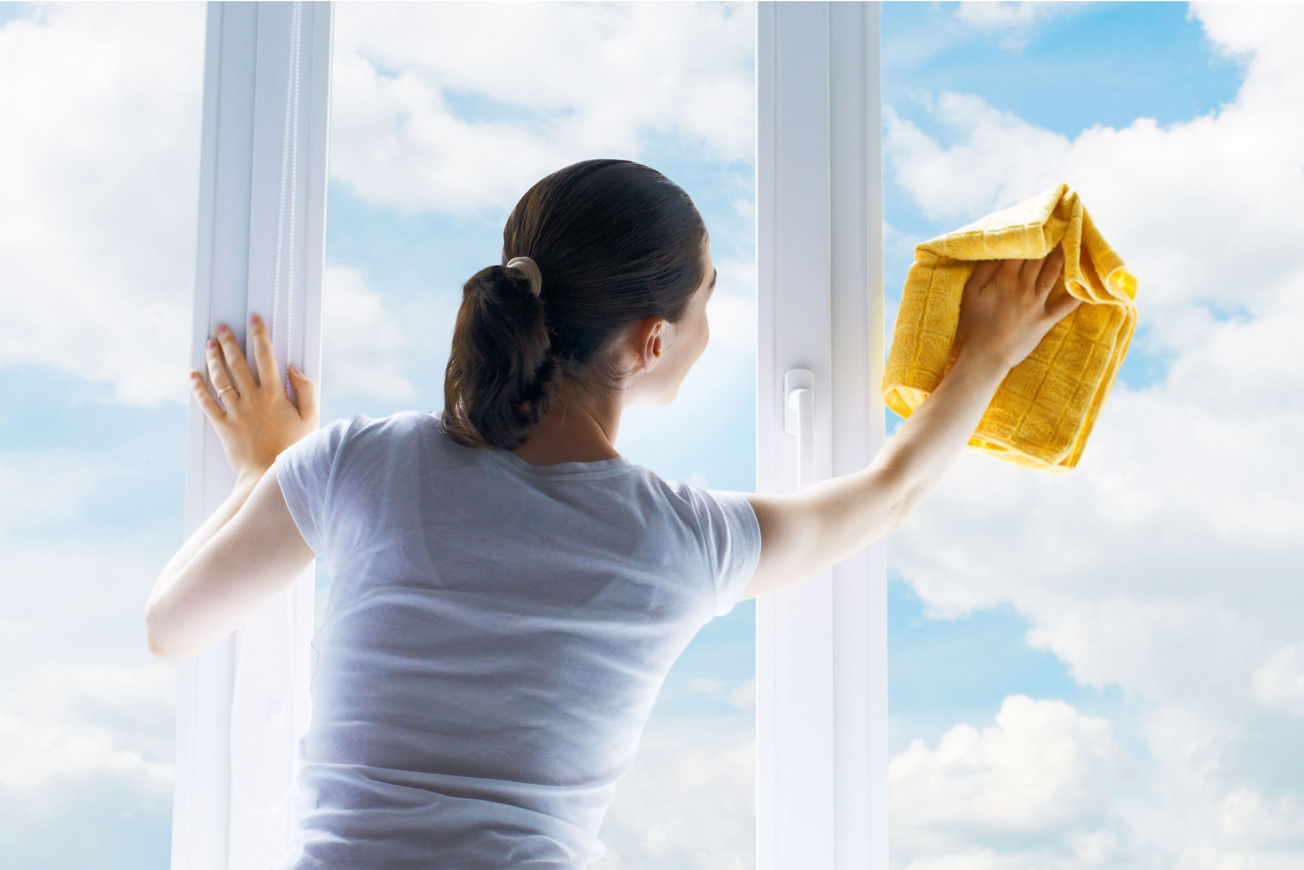 domestic helper wiping the window singapore image